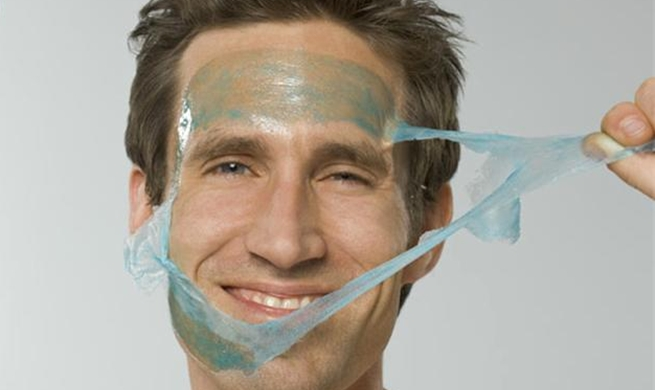 Close-up of mid adult man peeling facial mask