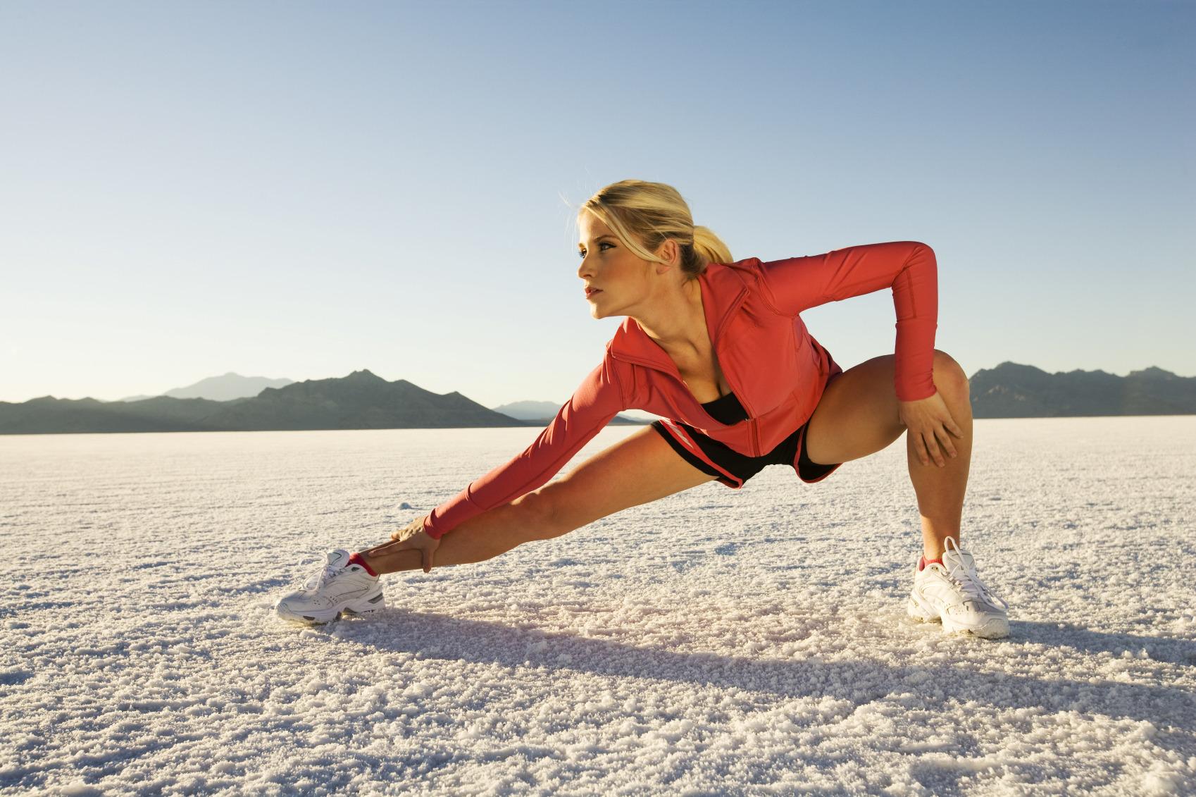 Mujer realiza estiramientos en una superficie de arena